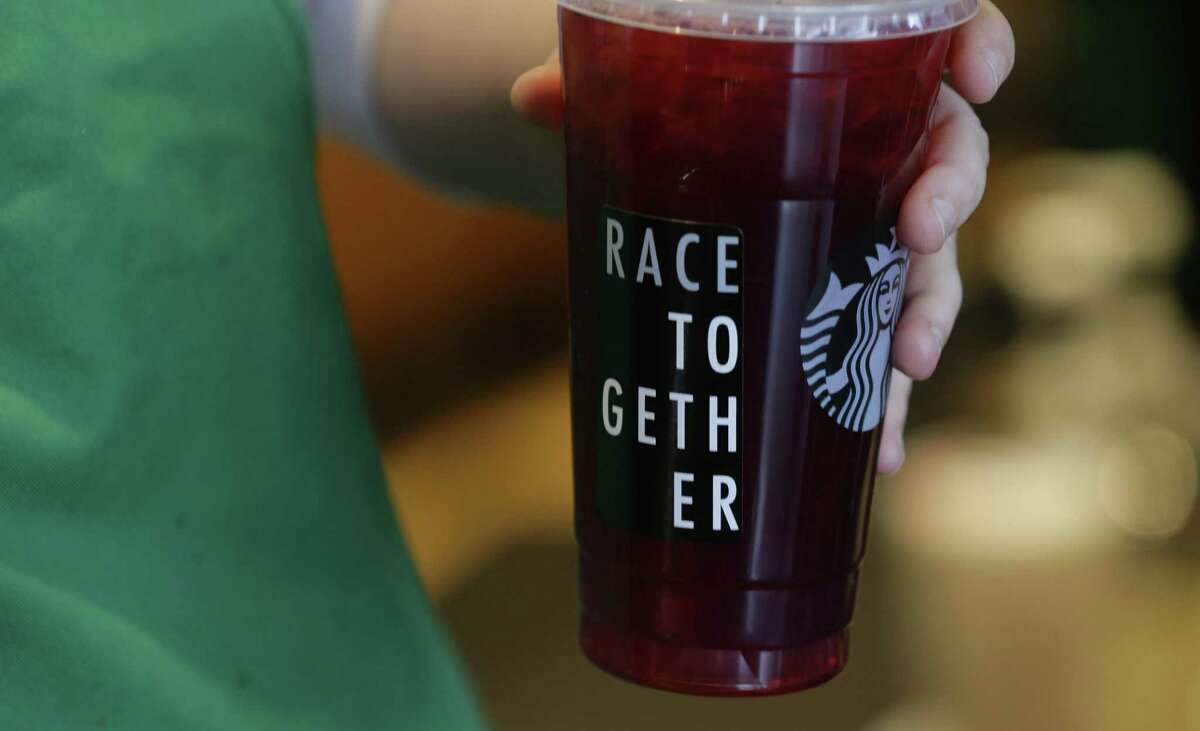 In this March 18, 2015, photo, a Starbucks barista holds an iced tea drink with a