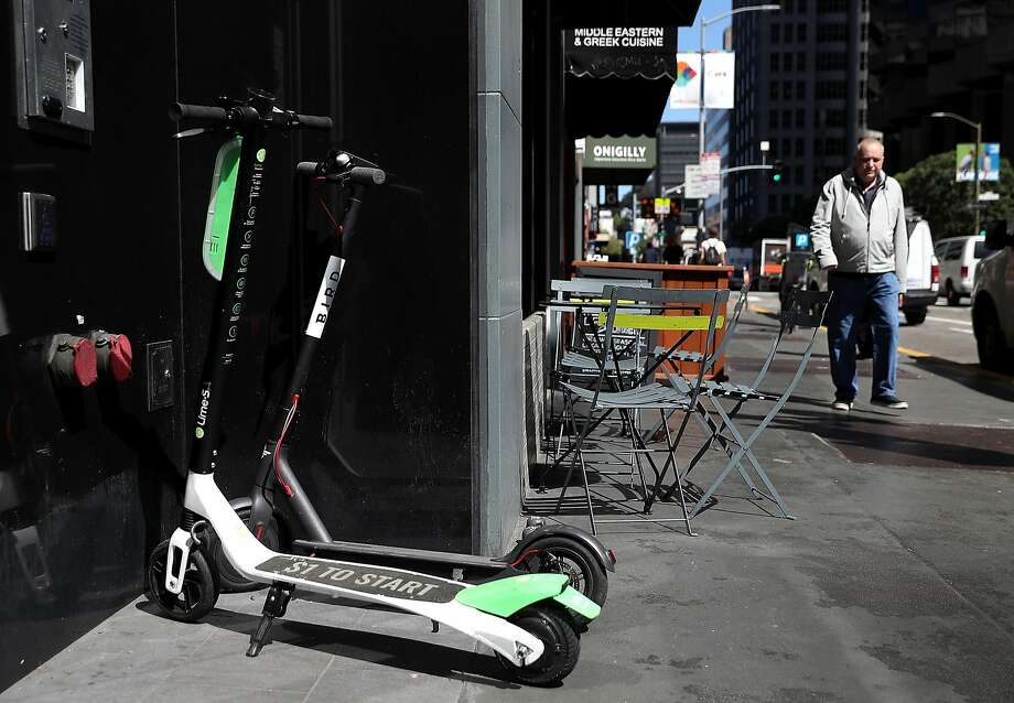 File photo of a Lime and Bird scooter parked in front of a building in San Francisco. Photo: Justin Sullivan / Getty Images