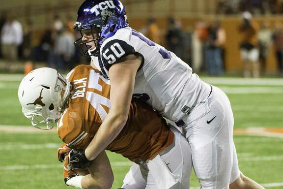 TCU's James Power (50) and Nick Orr (18) tackle Texas' Andrew Beck (47) during the first half of an NCAA college football game, Thursday, Nov. 27, 2014, in Austin, Texas. (AP Photo/Ashley Landis)