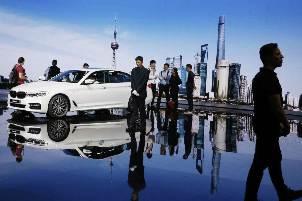 In this April 19, 2017, photo, visitors look at the BMW 5 series vehicle displayed at the Auto Shanghai 2017 show at the National Exhibition and Convention Center in Shanghai, China. China has announced plans to allow full foreign ownership of automakers in five years, ending restrictions that have strained relations with Washington and other trading partners.