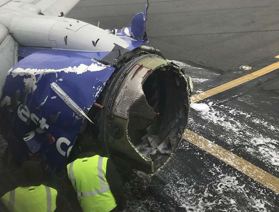 The engine on a Southwest Airlines plane is inspected as it sits on the runway at the Philadelphia International Airport after it made an emergency landing in Philadelphia, Tuesday, April 17, 2018. (Amanda Bourman via AP) Photo: Amanda Bourman, Associated Press