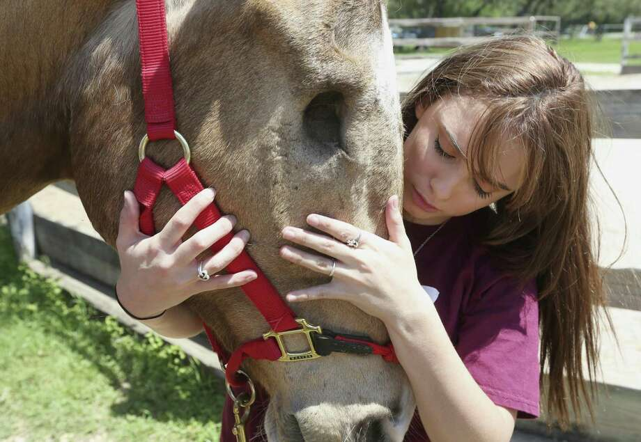 Kayla Reinagel takes a moment with her horse, Tonka, Thursday, April 12, 2018 before committing to the Schreiner University equestrian team. Reinagel, who is legally blind, received a $40,000 scholarship to attend the Hill Country school. Reinagel's horse lost his right eye in an accident seven years ago before Reinagel adopted him. Photo: William Luther, Staff / San Antonio Express-News / © 2018 San Antonio Express-News