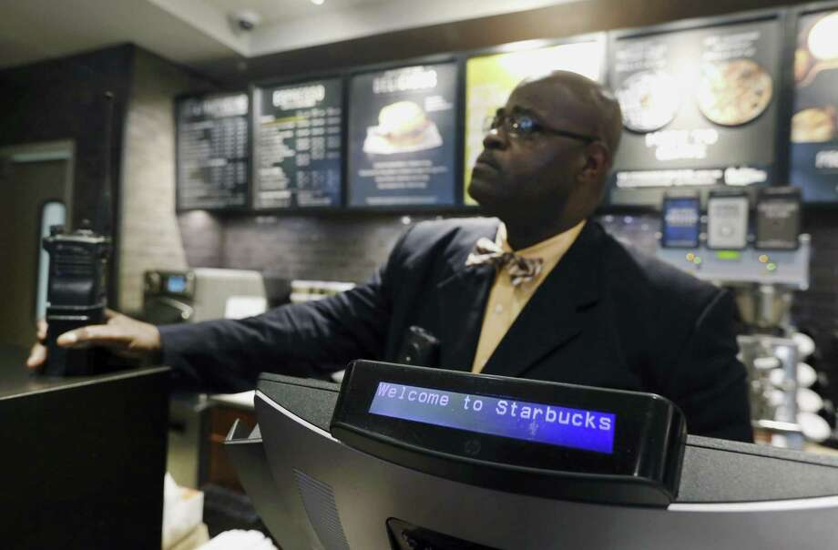 "A plain-clothed police officer mans a position behind the counter at the Starbucks that has become the center of protests in Monday, April 16, 2018, in Philadelphia. Starbucks wants to add training for store managers on ""unconscious bias,"" CEO Kevin Johnson said Monday, as activists held more protests at a Philadelphia store where two black men were arrested after employees said they were trespassing. (AP Photo/Jacqueline Larma) Photo: Jacqueline Larma, STF / Associated Press / Copyright 2018 The Associated Press. All rights reserved."