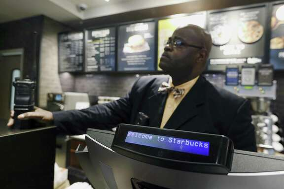 "A plain-clothed police officer mans a position behind the counter at the Starbucks that has become the center of protests in Monday, April 16, 2018, in Philadelphia. Starbucks wants to add training for store managers on ""unconscious bias,"" CEO Kevin Johnson said Monday, as activists held more protests at a Philadelphia store where two black men were arrested after employees said they were trespassing. (AP Photo/Jacqueline Larma)"