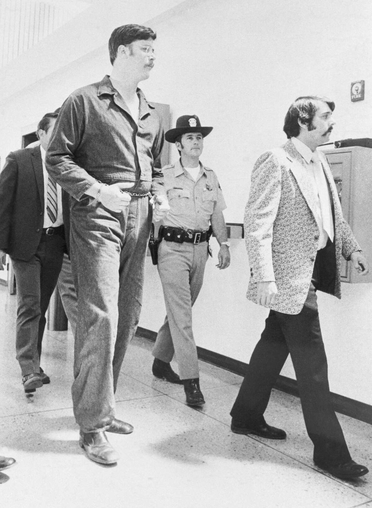 Edmund Kemper, 6-foot-9, towers over police officers as he's taken into custody.