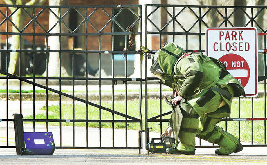 "A member of the Illinois State Police Bomb Squad sets up portable X-ray equipment to examine the contents of a suspicious package that was wrapped in a bluish-purple duct tape, covered with jack-o-lantern stickers, had a hand-printed label that read ""Please Open Me"" and was left leaning against the chained and locked fence at the entrance of Gordon Moore Park early Tuesday morning. Police blocked the entrance, called firefighters to the scene and summoned the bomb squad from Springfield. Police said the package contained nothing incendiary but would not elaborate on its contents. Photo:       John Badman 