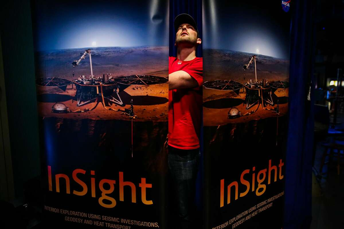 Scott Hulme organizes signage while setting up for the InSight Mars Lander Roadshow exhibit at the San Francisco Exploratorium in San Francisco, California, on Tuesday, April 17, 2018.