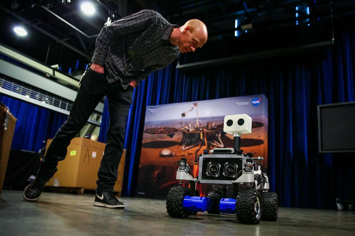 Rick Danielson checks out a ROV-E Mars rover model while setting up for the InSight Mars Lander Roadshow exhibit at the San Francisco Exploratorium in San Francisco, California, on Tuesday, April 17, 2018.