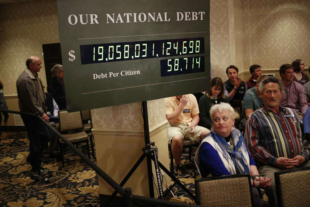 Attendees on March 28, 2016 sit beneath a rendition of the U.S. national debt clock at an event for John Kasich, governor of Ohio and 2016 Republican presidential candidate, in Madison, Wis.