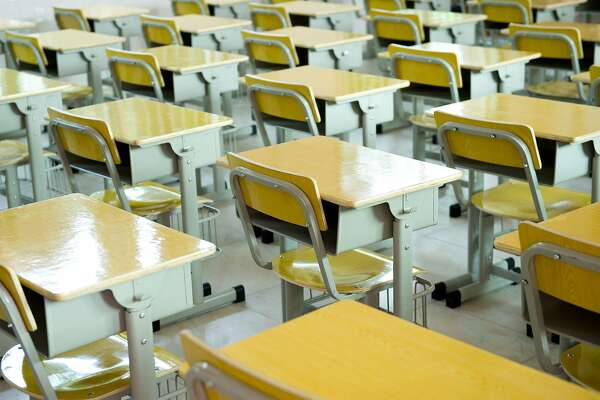 desk and chairs in classroom.    FOTOLIA