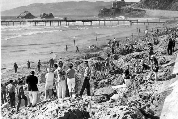 Emperor Norton Treasure Hunt 1960. Ocean Beach was packed as people dug for the golden medallion, May 26, 1960  You can see the Cliff House in the background, along with a pipe running into the ocean Photo ran 05/28/1960, p. 2