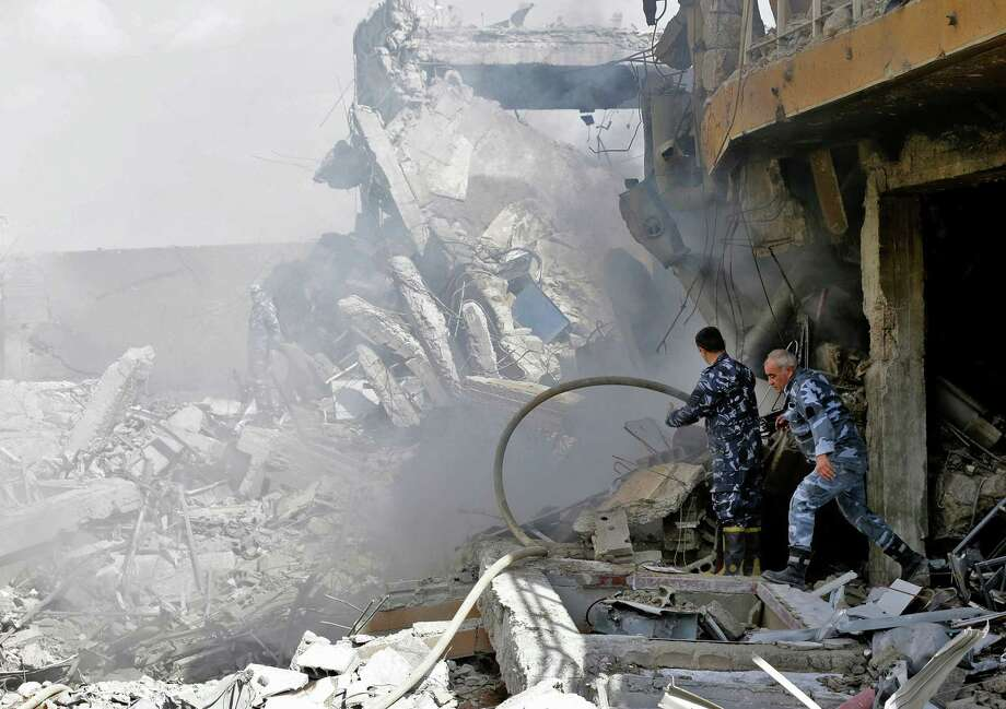 """Syrian soldiers inspect the wreckage of a building described as part of the Scientific Studies and Research Centre (SSRC) compound in the Barzeh district, north of Damascus, during a press tour organised by the Syrian information ministry, on April 14. The United States, Britain and France launched strikes against Syrian President Bashar al-Assad's regime early on April 14 in response to an alleged chemical weapons attack after mulling military action for nearly a week. Syrian state news agency SANA reported several missiles hit a research centre in Barzeh, north of Damascus, """"destroying a building that included scientific labs and a training centre."""" Photo: LOUAI BESHARA, Contributor / AFP/Getty Images / AFP or licensors"""