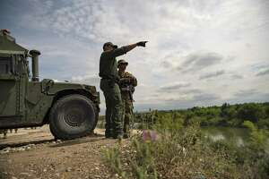 A Border Patrol officer talked with a member of the Texas National Guard along the Rio Grande in Starr County, Texas on April 10. As the National Guard begins a controversial mobilization on the southern border, soldiers are trying to fulfill two seemingly contradictory missions: standing out, and blending in.