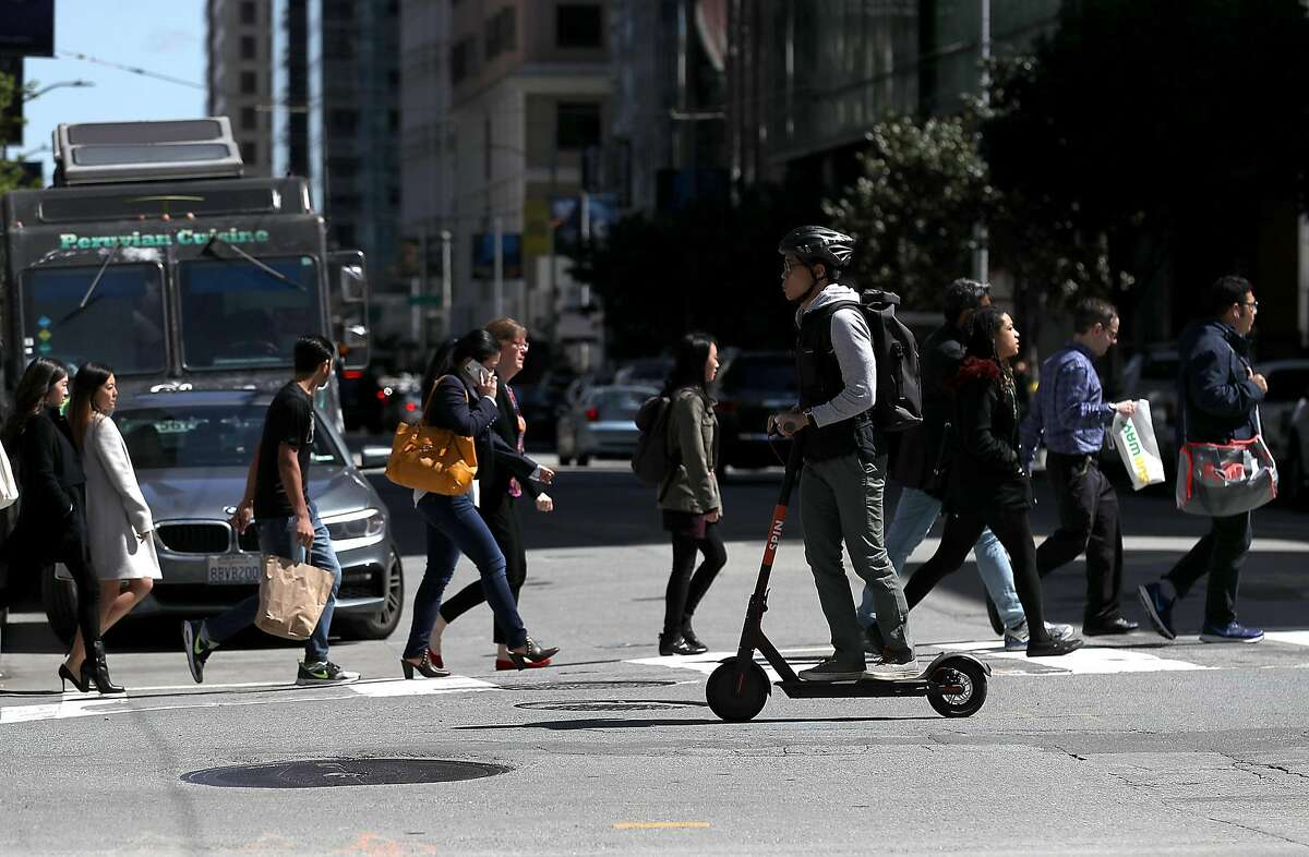 A user rides a Spin scooter on April 17, 2018 in San Francisco, California. Three weeks after three companies started placing electric scooters on the streets for rental, San Francisco City Attorney Dennis Herrera issued cease-and-desist notice to electric scooter rental companies Bird, LimeBike and Spin. The notice comes as the San Francisco board of supervisors considers a proposed ordinance to regulate the scooters to keep people from riding them on sidewalks, parking them in the middle of sidewalks and requiring riders to wear helmets and have a drivers license.