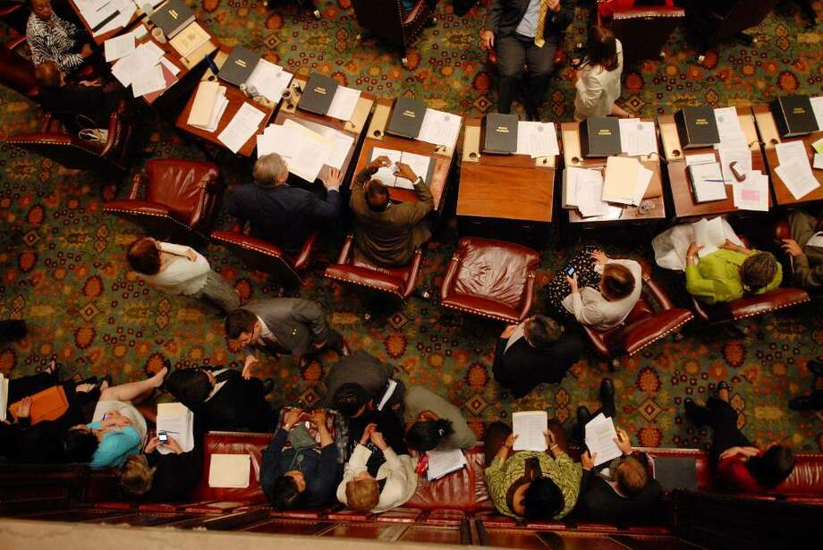 Senators work at their desks as their staff members are seated behind them on the floor of the Senate chambers at the Capitol in Albany on Monday, June 21, 2010.   (Paul Buckowski / Times Union) Photo: PAUL BUCKOWSKI