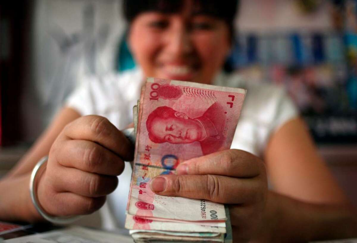 A bookstore vendor counts Chinese renminbi notes in Chengdu in southwest China's Sichuan province on Monday. China followed through Monday on its pledge to allow greater flexibility in exchange rates but said an appreciation in its currency alone could not rebalance world growth as it urged world leaders to carry out more fundamental reforms. (AP Photo)
