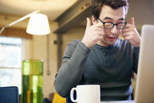 Stock image.Young man with laptop at home rubbing his eyes.