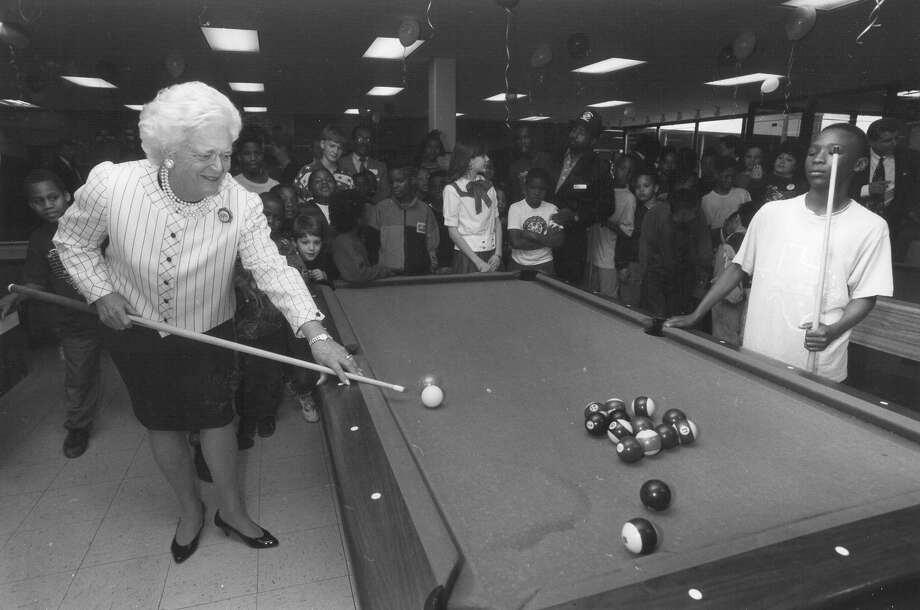 First Lady Barbara Bush plays pool with 12-year-old Tyrone Darden at the East Branch of the Boys & Girls Clubs of San Antonio on Feb. 26, 1992. Tyrone said later he thought he was playing with Texas Gov. Ann Richards. 