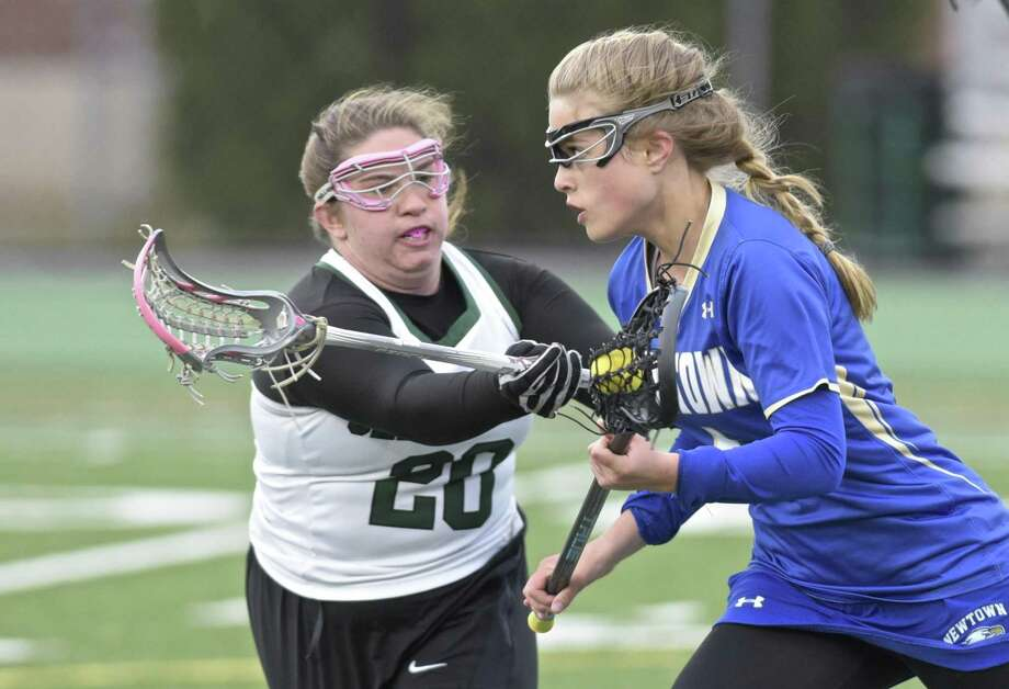 New Milford's Hannah Clark (20) defends Newtown's Lindsey Merrifield during their girls lacrosse game Tuesday at New Milford High School. Photo: H John Voorhees III / Hearst Connecticut Media / The News-Times
