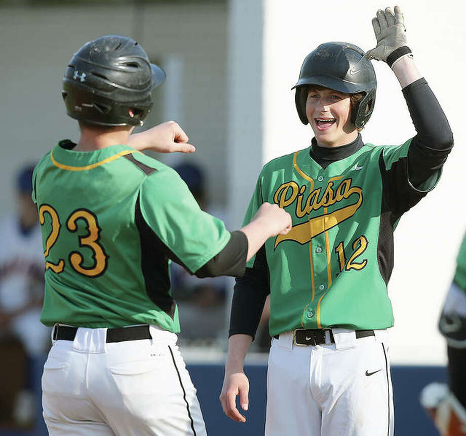 Southwestern's Eddie Bolin (23) is congratulated by Chase Stahl (12) after hitting a three-run home run during the fourth inning of a game in Roxana on Tuesday. Credit: Billy Hurst - For the Telegraph Photo:       Billy Hurst | For The Telegraph