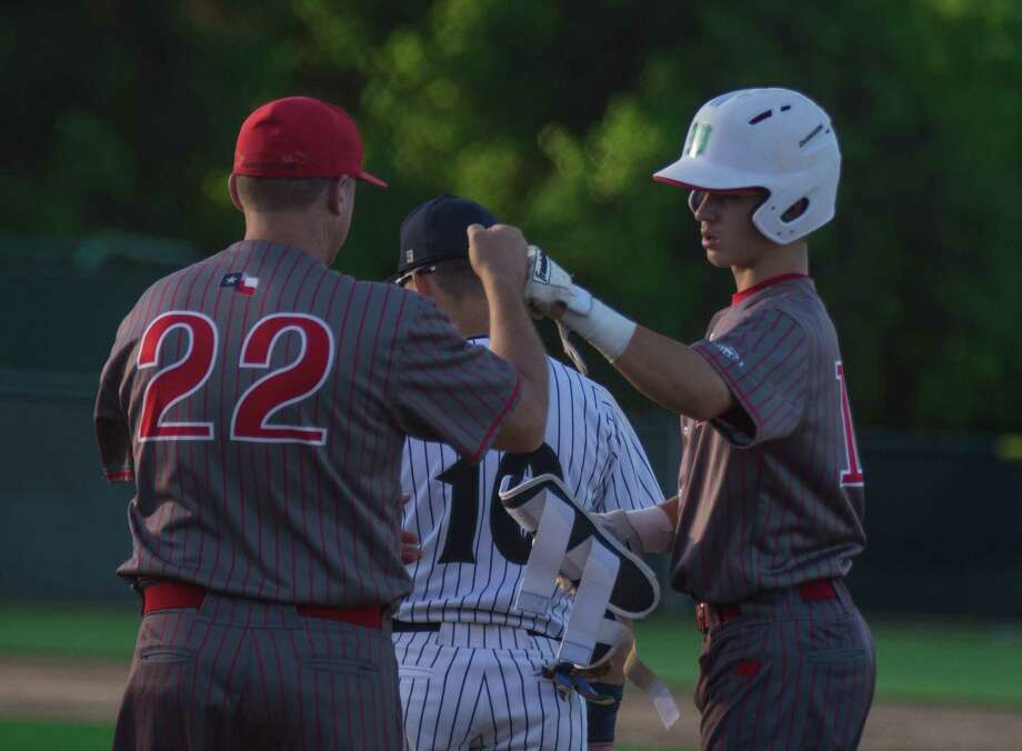 The Woodlands' Cameron Caley is congratulated after reaching base in the third inning against College Park on Tuesday at College Park High School in The Woodlands. Photo: Keith MacPherson