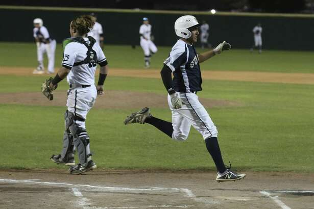 O'Connor's Mauro Bustamante (center) runs over homeplate to score the second of two runs in the first inning as Clark catcher Ben Hooper looks for the throw to home during their District 28-6A high school baseball game on Tuesday, Apr. 17, 2018. (Kin Man Hui/San Antonio Express-News)