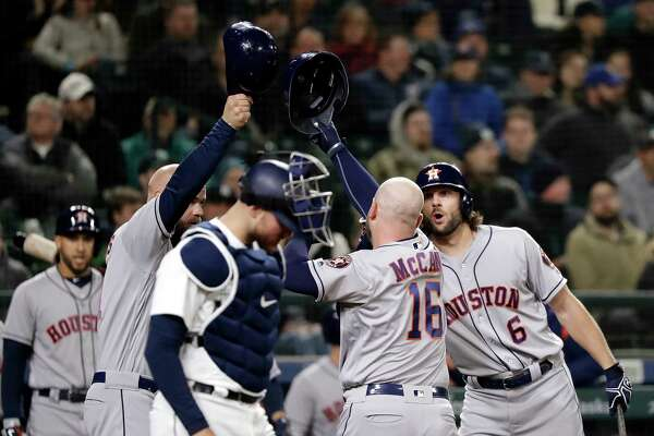 Seattle Mariners catcher Mike Marjama looks down as Houston Astros players celebrate the two-run home run bu Brian McCann (16) during the sixth inning of a baseball game Tuesday, April 17, 2018, in Seattle. (AP Photo/Elaine Thompson)