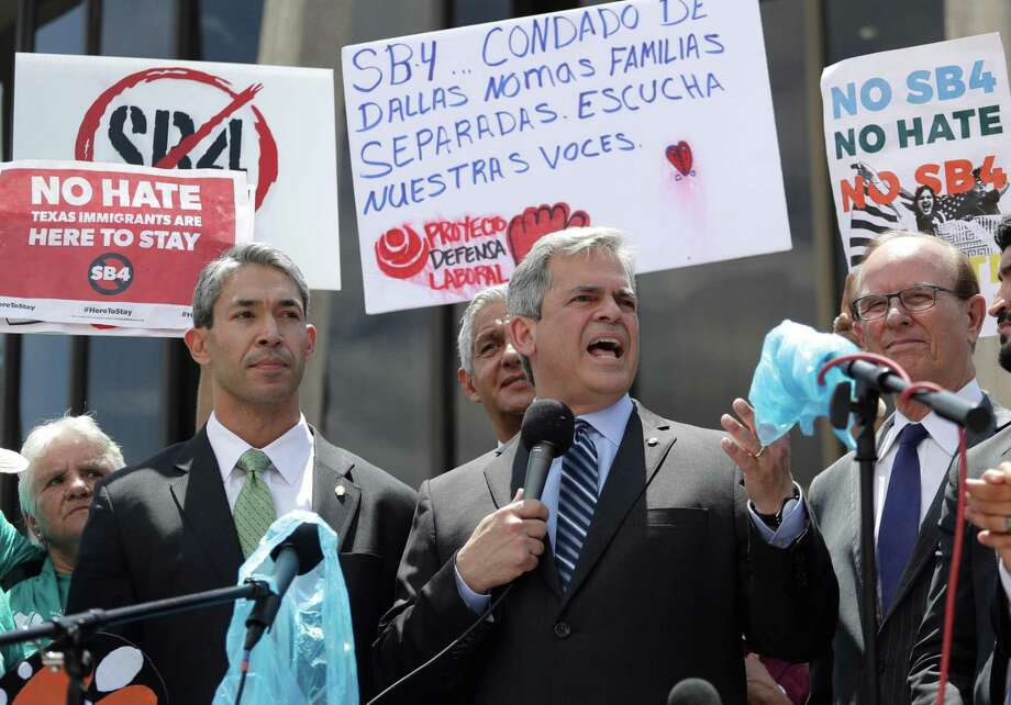 """FILE - In this Monday, June 26, 2017 file photo, Austin, Texas Mayor Steve Adler, center, stands with San Antonio Mayor Ron Nirenberg, left, as he speaks to protesters at a rally in San Antonio outside of the Federal Courthouse to oppose a new Texas """"sanctuary cities"""" bill that aligns with the president's tougher stance on illegal immigration. The census, undertaken every 10 years, uses the number of total residents _ not citizens _ to allot seats in the U.S. House of Representatives to each state. """"If we don't count all the people who live in our city _ all the residents we have _ it could mean that our community doesn't get our fair share of moneys or aid,"""" says Adler. (AP Photo/Eric Gay) Photo: Eric Gay, STF / Associated Press / Copyright 2018 The Associated Press. All rights reserved."""
