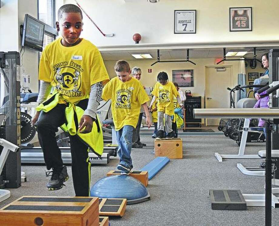 Ouindi Ngoma, a second-grader at Eisenhower Elementary, leads his classmates across a balance test set up Tuesday in the rehabilitation center at Passavant Area Hospital Auxiliary's Mini-Medical Days. This program is designed to help ease fear about the hospital by providing tours to students. Photo:       Audrey Clayton | Journal-Courier