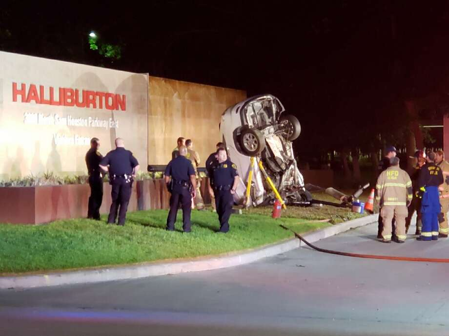 Officers And Emergency Officials Surround A Crashed SUV In Front Of The Halliburton Complex Houston