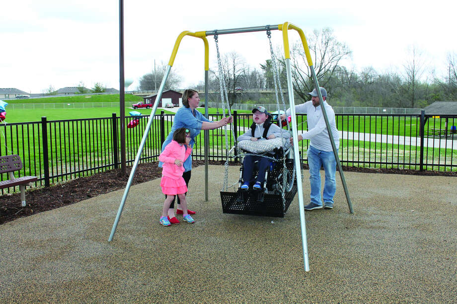 Kelan Masinelli gets a hand from sister Riley, mom Jamie and dad Tim as he tries out the special swing that bears his name in the Boundless Playground at Edwardsville Township Park on Saturday morning.