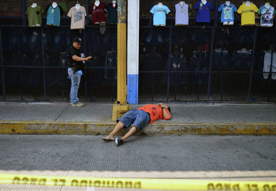 A prosecutor's office agent takes pictures of the corpse of a man executed by armed men who chased him off along Cuauhtemoc Avenue in the touristic city port of Acapulco, Guerrero state, Mexico on April 05, 2018.  Guerrero, which has some popular beach destinations such as Acapulco, Ixtapa and Zihuatanejo, is also one of the poorest states in the country and one of the hardest hit by organized crime violence. Photo: FRANCISCO ROBLES/AFP/Getty Images