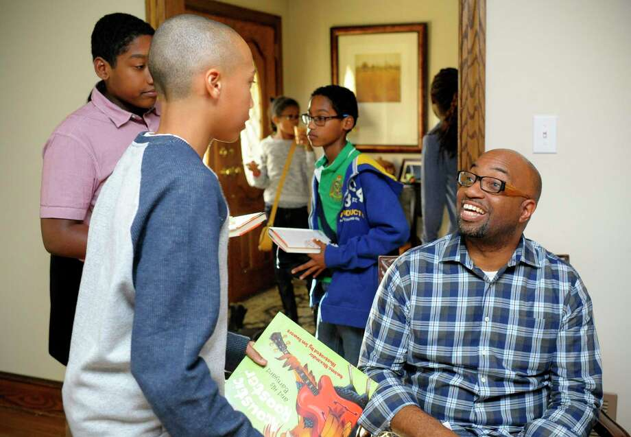 "Author and poet Kwame Alexander, who won the Newbery Medal for his book ""The Crossover,"" talks with kids at a 2015 book-signing event in Alexandria, Virginia. Photo: Washington Post Photo By Katherine Frey / The Washington Post"