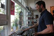 Josh Wright, owner of the Vinyl Street Cafe, browses through some of the records for sale at his Post Road shop last year. Record Store Day takes place on Saturday and Vinyl Street Cafe will open at 8 a.m. and have live music, giveaways and special guests.