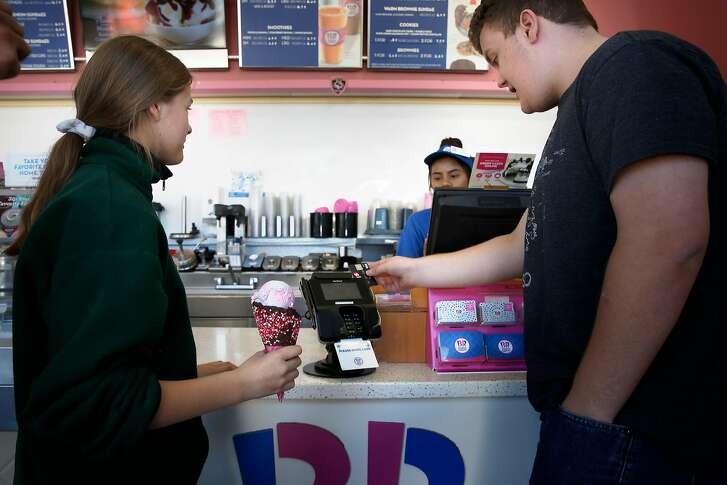 Avery Whann swipes his credit card through a Verifone device, treating his sister Alexandra Whann to an ice cream at the Baskin Robbins ice cream store in Mountain View, Ca., on Tues. April 17, 2018. Verfone is a company that provides the technology for electronic payment transactions. San Jose Verifone's board recently approved an acquisition offer by a private equity group.