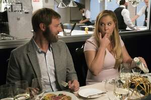 """This image released by STX Films shows Rory Scovel, left, and Amy Schumer in a scene from """"I Feel Pretty."""" (Mark Schafer/STX via AP)"""