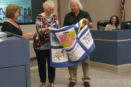Paula and Steve Boone unfold a quilt presented to them by Humble ISD physical education staff in appreciation of the Marathon Challenge they launched in Humble ISD 26 years ago.