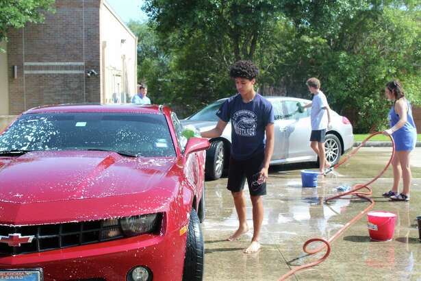 Kingwood High School students wash cars in the parking lot of RE/MAX at Kingwood Town Center on Wednesday, April 11, as a way to help fundraise for their Project Graduation event to occur in May.