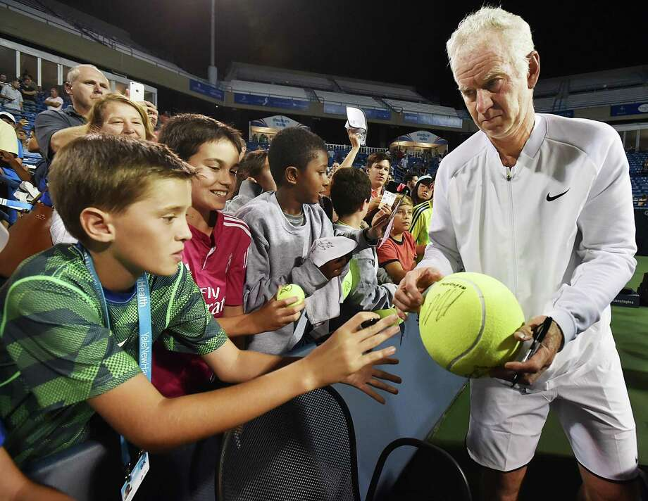 John McEnroe autographs and hands off a giant tennis ball to Albert Bostoen, 12, of Westport, after losing 6-4,  to James Blake in the Men's Legends match, Thursday night, August 25, 2016, at the Connecticut Open at Yale University in New Haven. Spencer Quinn, 12, of Weston and Tyson Nichols, 12, of Redding look on. (Catherine Avalone/New Haven Register) Photo: Catherine Avalone / New Haven RegisterThe Middletown Press