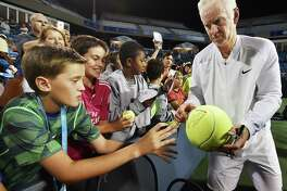 John McEnroe autographs and hands off a giant tennis ball to Albert Bostoen, 12, of Westport, after losing 6-4,  to James Blake in the Men's Legends match, Thursday night, August 25, 2016, at the Connecticut Open at Yale University in New Haven. Spencer Quinn, 12, of Weston and Tyson Nichols, 12, of Redding look on. (Catherine Avalone/New Haven Register)