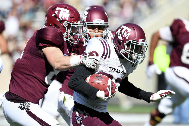 Texas A&M's Jace Sternberger (81) attempts to tackle Roney Elam (27) following an interception in the second quarter Saturday during the Maroon & White spring game at Kyle Field.