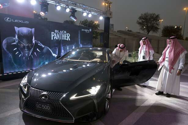 """A visitor checks out a Lexus car, similar to a one used in the film """"Black Panther,""""  that is on display outside an invitation-only screening, at the King Abdullah Financial District Theater, in Riyadh, Saudi Arabia, Wednesday, April 18, 2018. Saudi Arabia will hold a private screening of the Hollywood blockbuster """"Black Panther""""  Wednesday, to herald the launch of movie theaters that are set to open to the public next month. (AP Photo/Amr Nabil)"""