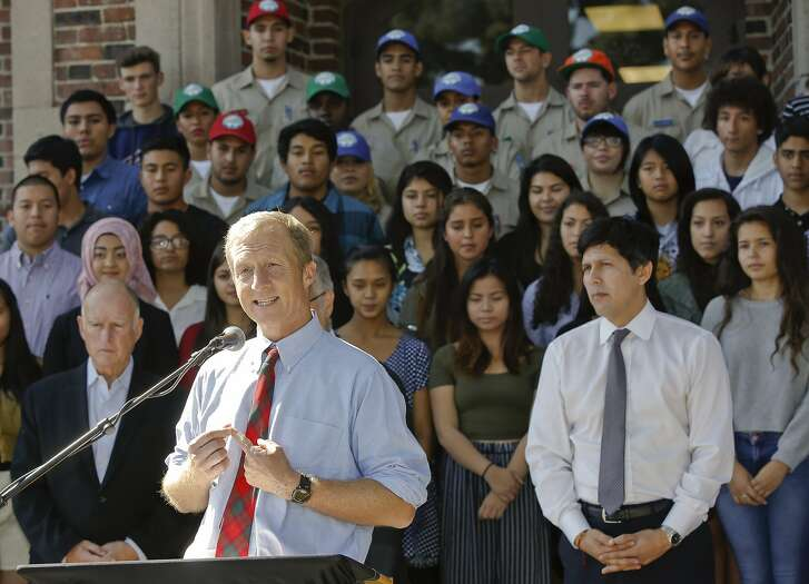 California Prop. 39 co-chair Tom Steyer, at podium, addresses students at John Marshall High School in Los Angeles Tuesday, Oct. 28, 2014. Marshall High School has been approved for $1,836,072 of Prop. 39 funds for energy projects including: new air systems for the auditorium and classrooms, lighting controls for the gym and other high-use areas, a new energy management system, and improved lighting throughout the campus. Gov. Jerry Brown, is seen bottom left, and Senate President pro Tempore Kevin de Leon, right. (AP Photo/Damian Dovarganes)