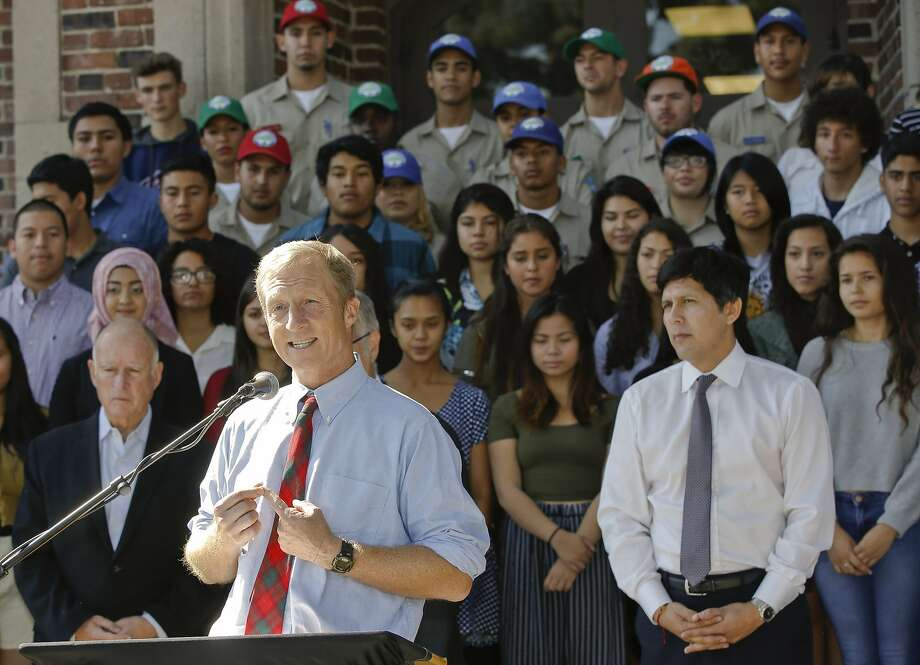 Tom Steyer, at podium, and state Sen. Kevin de Leon, right, with Gov. Jerry Brown, left, and students at John Marshall High School in Los Angeles during a clean-energy event in October 2014. Steyer endorsed de Leon for U.S. Senate on Wednesday in the challenger's race against Sen. Dianne Feinstein. Photo: Damian Dovarganes / Associated Press