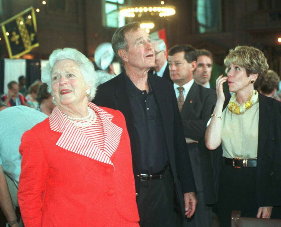Former President George Bush looks up toward his portrait that is hung on the wall in Yale Commons, a large dining hall at Yale University in New Haven, Conn., Friday, May 29, 1998. Bush was attending a 50th  reunion luncheon of his Yale class  and participated in the presentation of the portrait to Yale. At left is his wife, Barbara. Woman at right is unidentified.  (AP Photo/Bob Child) HOUCHRON CAPTION (05/31/1998): Former President George Bush, accompanied by wife Barbara, looks up toward his portrait that has been hung on the wall in Yale Commons, a large dining hall at Yale University in New Haven, Conn., on Friday. Bush was attending a 50th reunion luncheon of his Yale class and participated in the presentation of the portrait to Yale. Photo: BOB CHILD / AP / AP