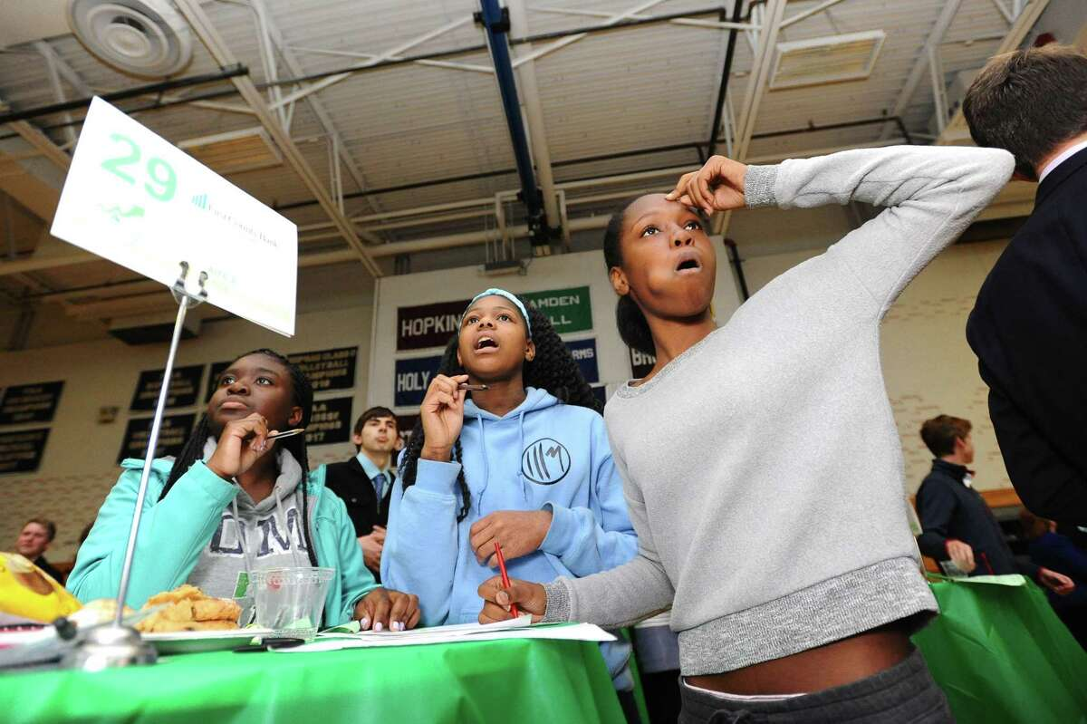 AITE sophomores, from right, Kim Louis, Ejine Ndokwu and Lindsey Frederic anxiously wait for their investments to pop up on the big screen during the Junior Achievement Student Stock Market Exchange Challenge inside King School's gymnasium in Stamford, Conn. on Wednesday, April 18, 2018.