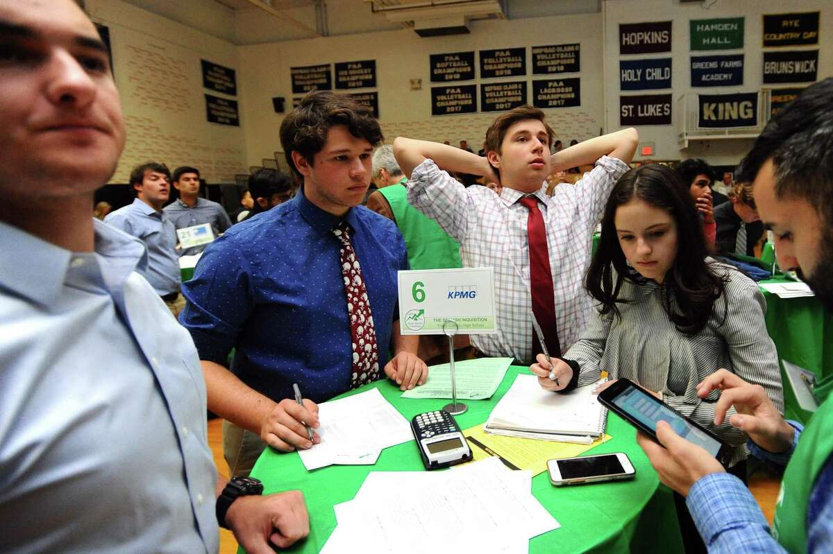16-year-old Tommy Alvarez, center right, puts his hands behind his head as he looks at his Trinity Catholic team's losing investments during the Junior Achievement Student Stock Market Exchange Challenge inside King School's gymnasium in Stamford, Conn. on Wednesday, April 18, 2018. Also pictured are Alvarez's Trinity Catholic teammates, from left, Collin McLaughlin, Jacob Lafort and Bella Martinez.