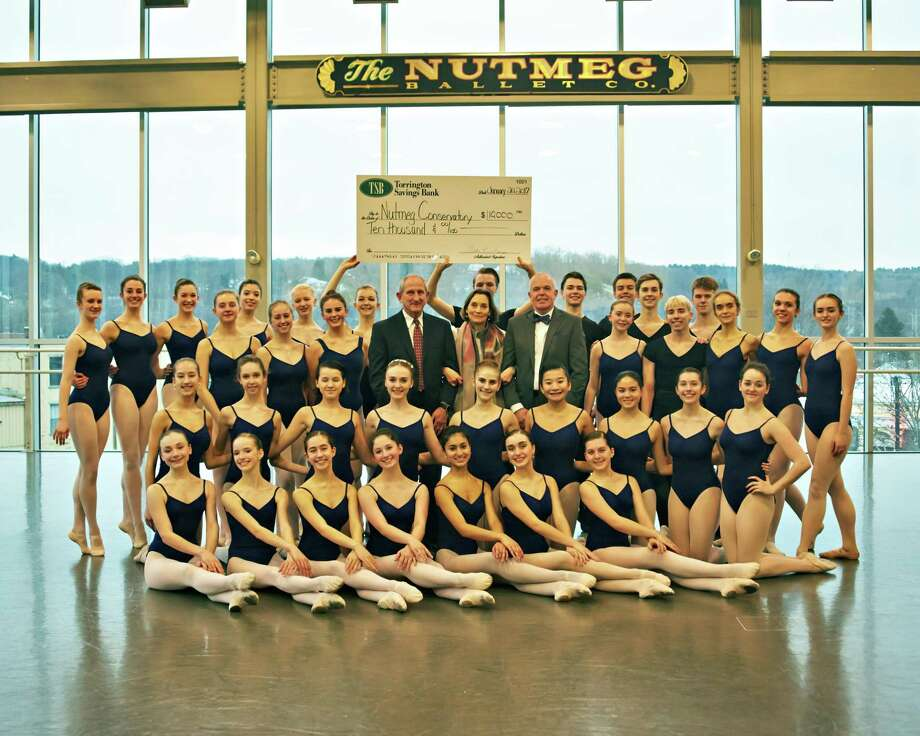 Nutmeg Ballet students display a check for $10,000 from Torrington Savings Bank in 2017 to help pay for new flooring for the dance studios at Nutmeg Conservatory. Standing at center are John E. Janco, president & CEO of Torrington Savings Bank; Victoria Mazzarelli, artistic director at Nutmeg Ballet Conservatory; and Jeff Geddes, senior vice president of residential & consumer lending and CRA officer at TSB. Photo: Photo Courtesy Of Torrington Savings Bank /