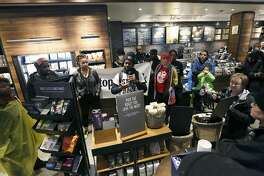 "Demonstrators occupy the Starbucks that has become the center of protests Monday, April 16, 2018, in Philadelphia. Starbucks wants to add training for store managers on ""unconscious bias,"" CEO Kevin Johnson said Monday, as activists held more protests at a Philadelphia store where two black men were arrested after employees said they were trespassing. (AP Photo/Jacqueline Larma)"