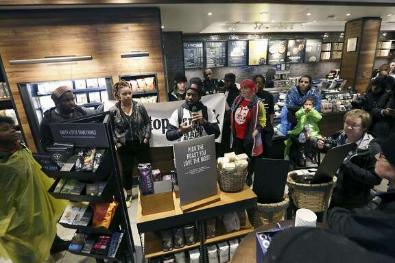 """Demonstrators occupy the Starbucks that has become the center of protests Monday, April 16, 2018, in Philadelphia. Starbucks wants to add training for store managers on """"unconscious bias,"""" CEO Kevin Johnson said Monday, as activists held more protests at a Philadelphia store where two black men were arrested after employees said they were trespassing. (AP Photo/Jacqueline Larma)"""